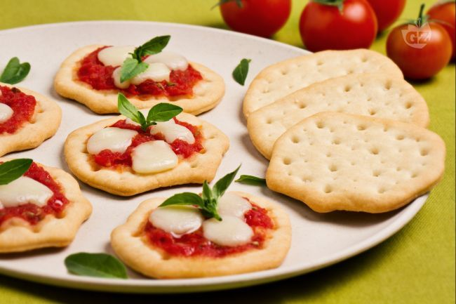 Le schiacciate pomodoro e mozzarella sono un gustoso antipasto finger food  a base di salsa di pomodoro aromatizzata all'origano e mozzarella filante.