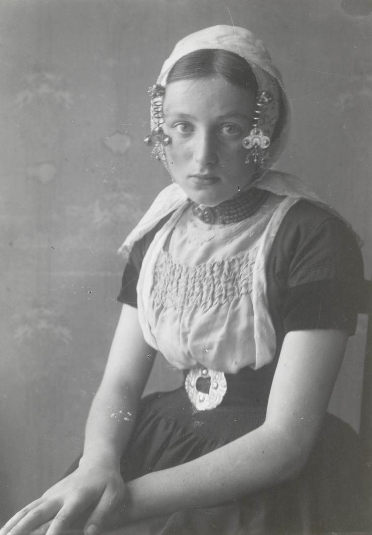 Meisje in Walcherse streekdracht. Het meisje is gekleed in kerkdracht. Een afgedankte zilveren schoengesp fungeert als ceintuurgesp. Aan de krullen van het oorijzer hangen oorijzerhangers, de zogenaamde 'strikken met waaiers', gedragen in bepaalde dorpen langs de kust van Walcheren. Molkenboer 1913-1916 #Zeeland #Walcheren