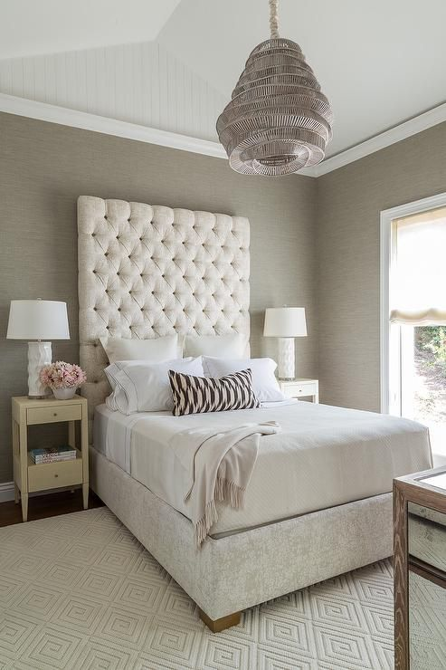 Cream and gray bedroom features a vaulted ceiling accented with a taupe woven pendant light illuminating walls clad in gray grasscloth lined with a tall cream velvet tufted headboard on bed dressed in white and gray hotel bedding flanked by cream nightstands and white rippled lamps atop a cream diamond woven rug.