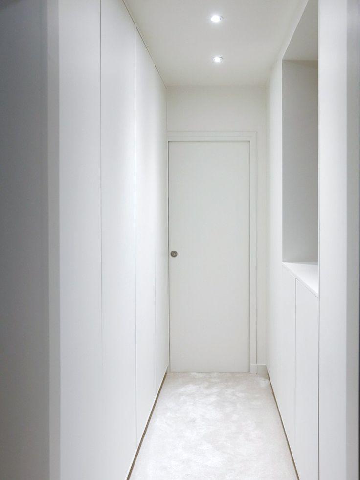 Dressing blanc sur-mesure, sans poignées, avec système d'ouverture push to open. Les portes ne descendent pas jusqu'au sol pour donner l'impression que le placard flotte au dessus du sol. La moquette blanche en laine crée une continuité avec la chambre attenante. Un éclairage LED est installé dans le placard, il se déclenche dès l'ouverture des portes.