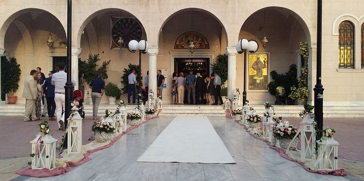 Ο εξωτερικός στολισμός του γάμου σας στην εκκλησία περιλαμβάνει πολλά χρώματα σε τριαντάφυλλα και πολλά φανάρια σε διάφορα μεγέθη με ένα ιβουάρ χαλί στο διάδρομο.