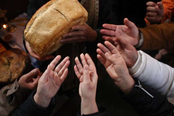 People reach for bread blessed by a priest during a religious ceremony, Porodine, Albanie, Andrei Pungovschi