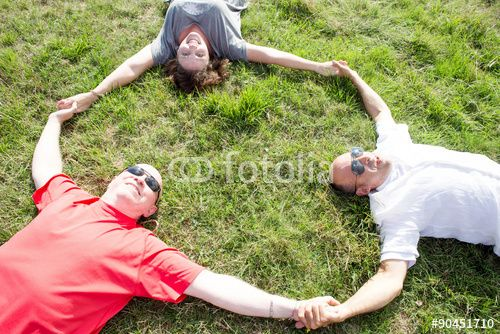 adults making circle symbol over green field