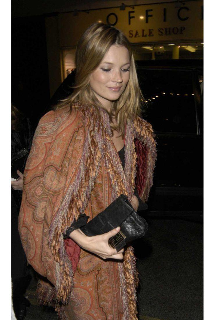 Kate Moss in boho rusty orange paisley printed, tassle-trimmed coat and black Fendi clutch bag.