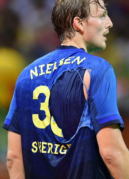 #TOPSHOT Sweden's pivot Jesper Nielsen looks on after his jersey was torn during the men's preliminaries Group B handball match Sweden vs Germany for...