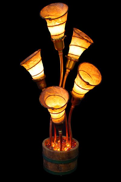 """Patanne""    Assembled from a small wooden barrel and hand-made shades created from the seat springs of an old pickup truck, these five trumpets glow warmly above a small inferno; several recessed flicker-flame bulbs set a shallow pool of glass rocks. (w:16"" h:33"" d:15"")    $1,300.00"