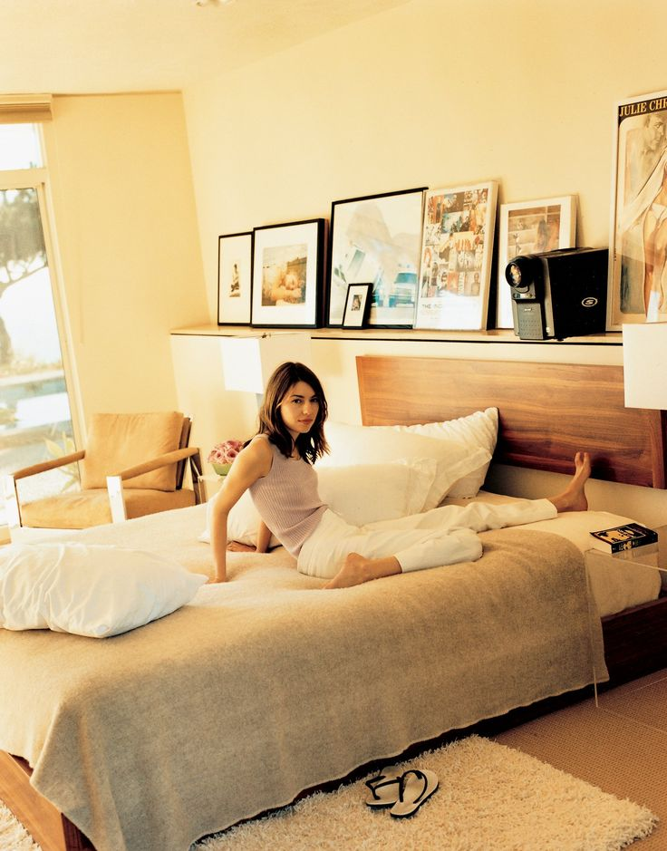 Sofia Coppola, in her mid-century-modern bedroom, complete with shag rug and vintage fashion photography.