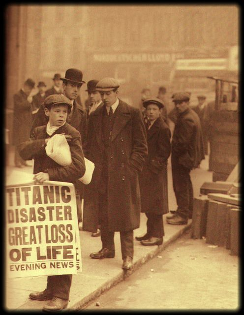 "London street scene, 1912. A newsboy holds a broadside reading, ""Titanic Disaster Great Loss of Life."""
