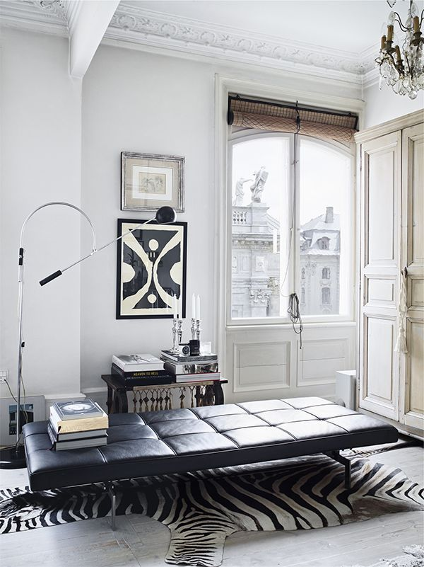 A dreamy black and white apartment with crown mouldings, leather daybed and zebra hide rug.