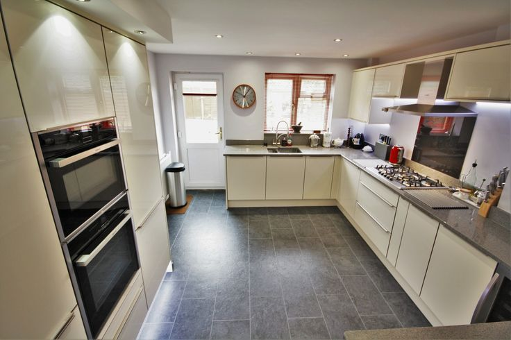 Cream Acrylic gloss kitchen design, with a Grey Quartz worktop.