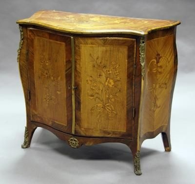 A George III Kingwood, Rosewood And Floral Marquetry Serpentine Commode, In  The Manner Of
