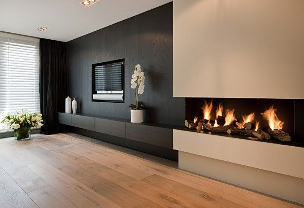 slim contemporary fireplace in cream continuing from black feature wall