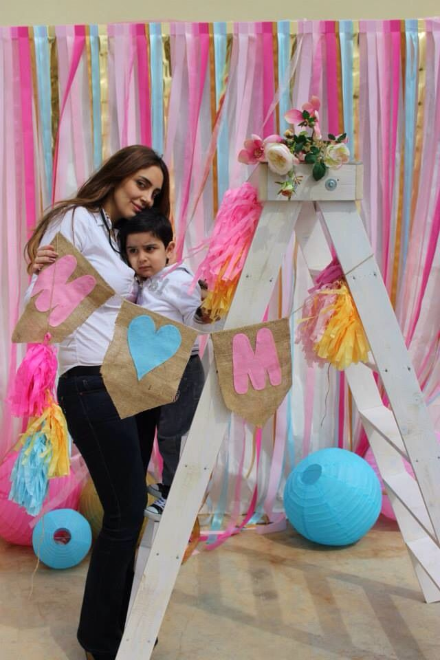 Ribbon Wall back drop for Mother's Day. Banner with tassels. Tissue paper tassels. Chinese lanterns. Ladder. Mother's Day event. Photo booth. Ribbon background. Mom. Pink. Blue. Gold. White. Mom banner. Photoshoot with mom.
