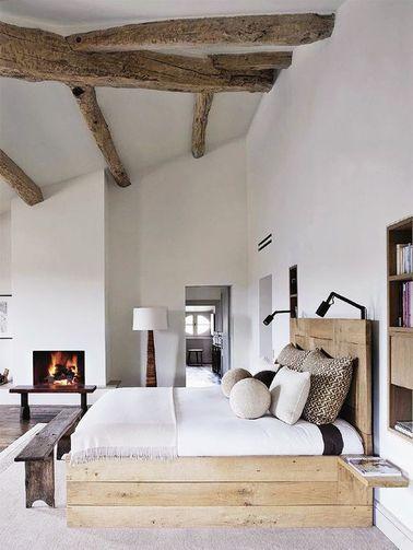 Une chambre avec poutres brutes et un grand lit palette
