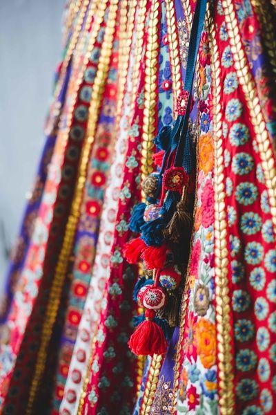 Bridal Details - Bridal Threadwork Sabyasachi Lehenga with Red and Blue Pom-Poms | WedMeGood |  #wedmegood #bridaldetails #threadwork #panels #indianbride #indianwedding #lehenga