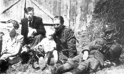 """Lato 1946; od lewej: sanitariuszka Krystyna Wiśniewska """"Dzikuska"""", Kazimierz Pawłowski """"Nerw"""", Marian Pawełczak """"Morwa"""" (z dzieckiem na kolanach), Eugeniusz Siekaczyński """"Ślipek""""."""