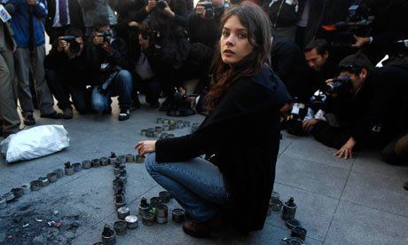 Chilean student leader Camila Vallejo sits among a peace sign created from empty teargas canisters used by police against protesters. Photograph: Roberto Candia/AP