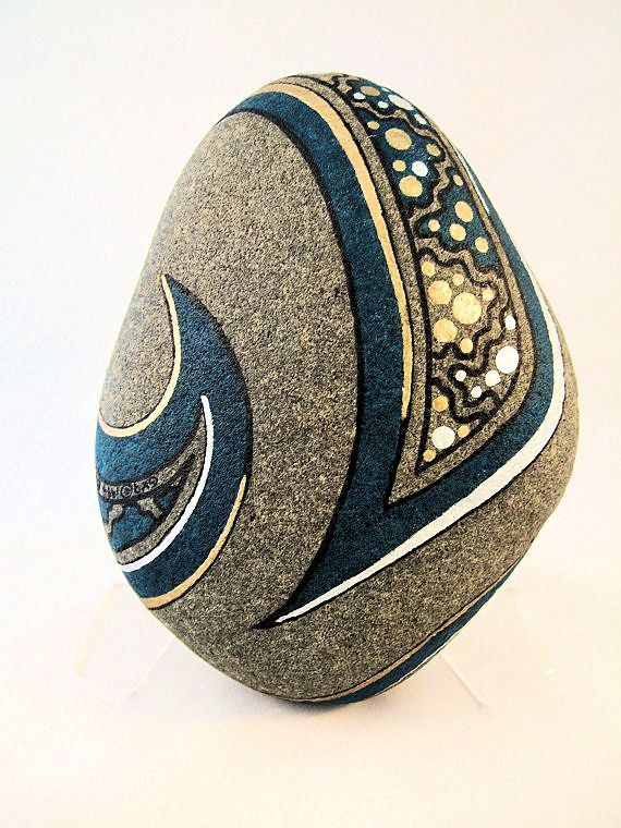 Unique art zen art painted rock 3d art ornaments signed numbered dated artwork. This is an original signed collectibles artwork and you will not find another one like it anywhere. The gorgeous design has metallic gold and silver galaxy stars on a turquoise blue background. It comes with a clear white acrylic easel that it can sit on so that the rock can be rotated in different directions to present a variety of faces, as your mood dictates. The photographs show the front side and the back…