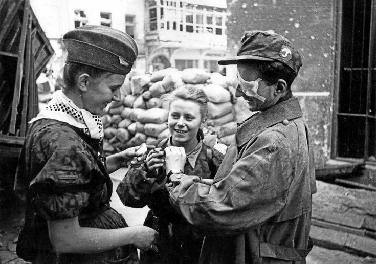 Dwie sanitariuszki i ranny powstaniec z batalionu 'Parasol' po wyjściu z kanału na ulicy Wareckiej przy Nowym Świecie. Pośrodku stoi Maria Stypułkowska- -Chojecka 'Kama'. Po prawej Krzysztof Palester 'Krzych'.
