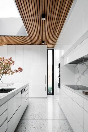 The width of the corridor leading to the kitchen frames the island bench and the skylight above.