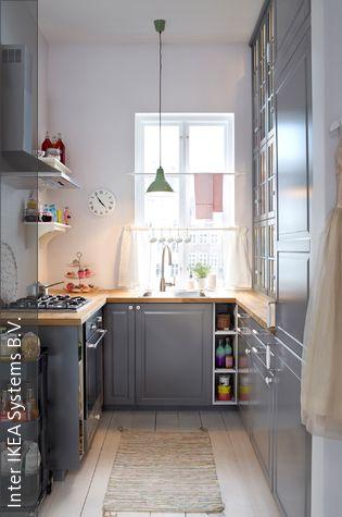 Das hohe Schranksystem in Grau bietet auch in der kleinen Küche Stauraum für alles, was das Herz eines Koch-Fans begehrt. Die Stangen vor dem Fenster können zum Beispiel als Handtuchhalter dienen.