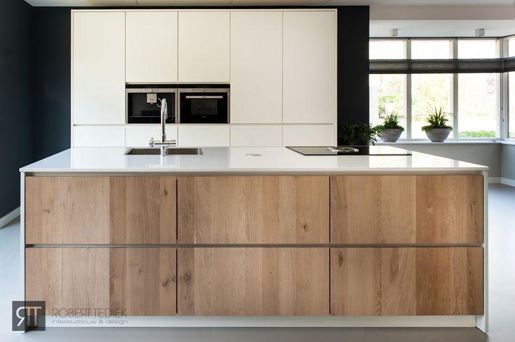 Moderne keuken met strakke wit gespoten fronten en in het eiland massief eiken fronten voor een moderne maar toch warme uitstraling.