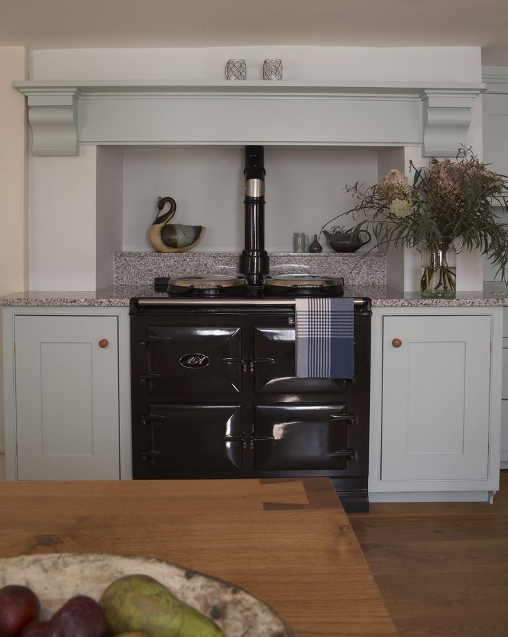 Classic English cabinetry surround a classic black Aga! This beautiful kitchen is painted in Farrow & Ball Theresa's Green with a Sardinia Grey granite worksurface.