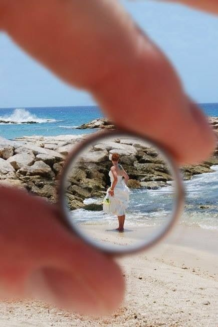 Keep it in perspective with this unique wedding photo composition. Focus on the bride, as seen through the wedding ring, while at the beach.
