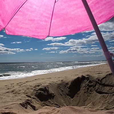 Pink beach umbrella in the sand