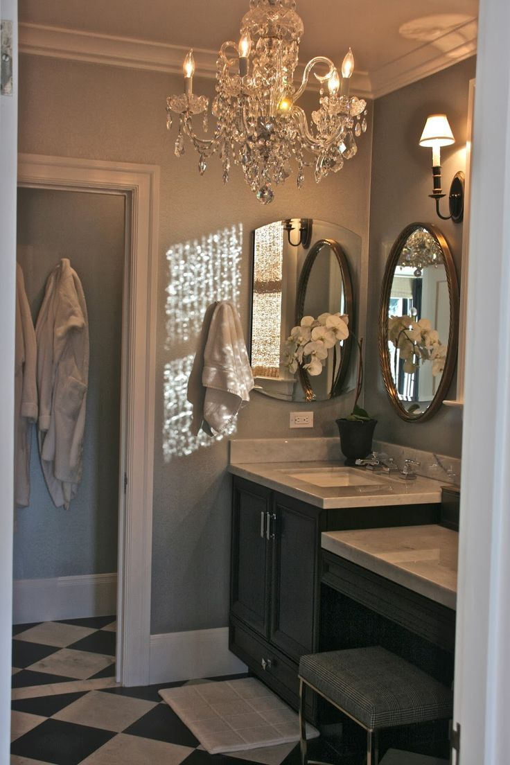 elegant retreat. . .oval mirror framed in cherry, silvery blue on the walls, crystal chandelier, and rattan shades