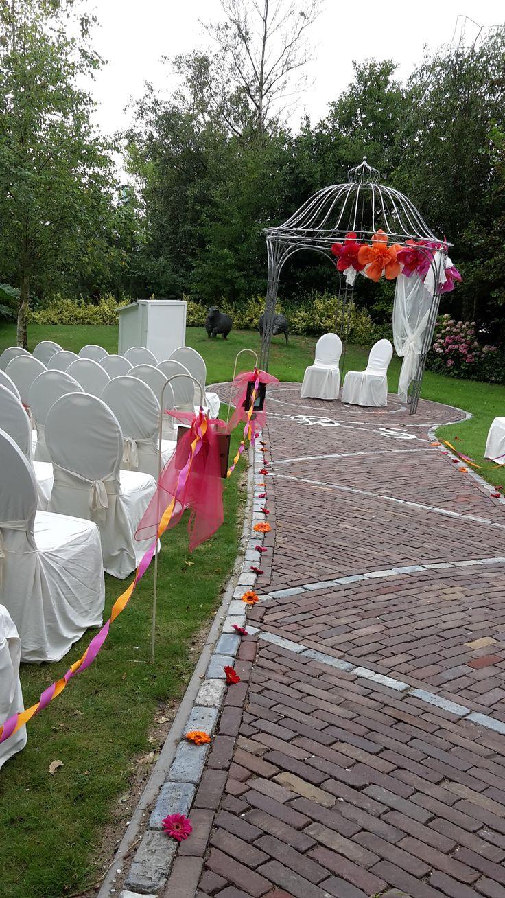 Prieeltje met grote papieren bloemen en organza. Looppad met gerbera's, paaltjes met foto's van de bruid en gom: van baby tot heden...en linten in fuchsia en oranje! Stoer! Kijk op www.defeesttuin.nl om dit allemaal te huren.