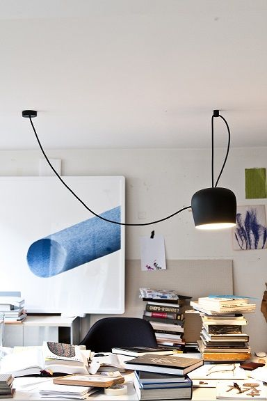 FLOS Aim pendant lighting by Ronan and Erwan Bouroullec brightens a busy white office space featuring contemporary artwork and a plethora of books.