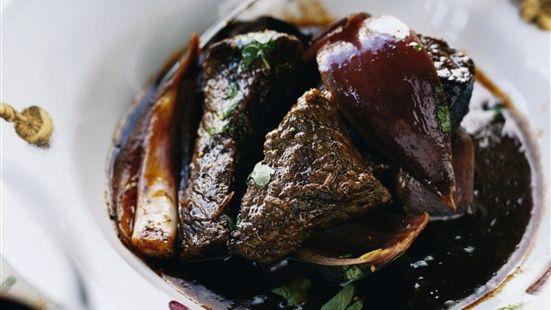 Bryn köttet i olivolja i en gryta tills det fått fin färg. Lägg i vitlök, kryddor, tomatpuré och bryn ytterligare någon minut. Häll på vin, balsamico, buljongtärningar och vatten. Låt sjuda under lock 1½–2 timmar. Koka med rödlöken de sista 20 minuterna. Smaka av med salt och peppar. Strö över persilja. Servera med sallad och ett gott bröd.
