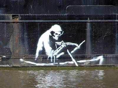 Banksy is the guy who arrives quietly by night in various big cities and puts up fresh graffiti, generally in the form of life-sized stencils.  This is a stencil on the waterline of The Thekla, an entertainment boat in central Bristol It's the image of Death baed on a nineteenth-century etching illustrating the pestilence of The Great Stink.