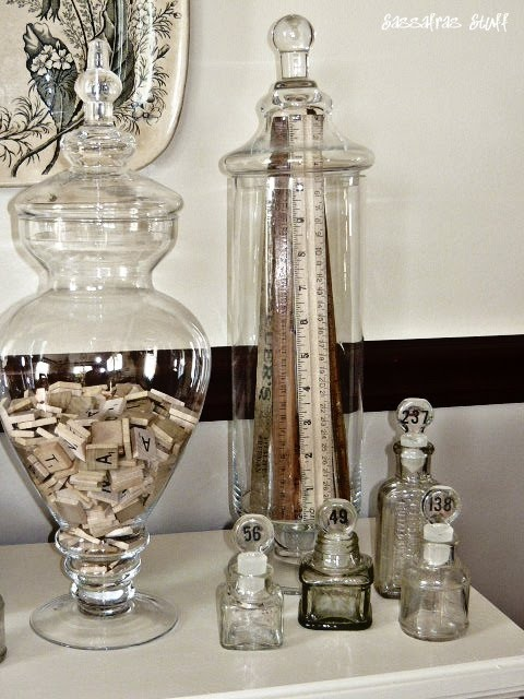 Tall jar full of rulers and giant apothecary jar filled with vintage game pieces