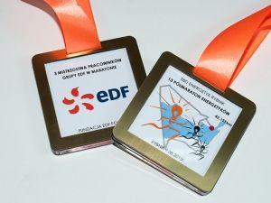Medal z okazji zorganizowania Półmaratonu Energetyków przez pracowników firmy EDF. Medale kwadratowe z laminatu grawerskiego w złotym kolorze, z kolorowym nadrukiem.