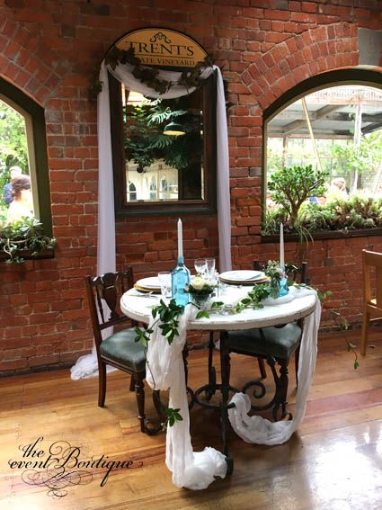 Gorgeous white and iron table and dusky blue chairs from our boutique collection, styled as a sweetheart table, with soft muslin, jasmine, blue bombay bottles, crystal and boutique table settings to create a romantic table for the bride and groom