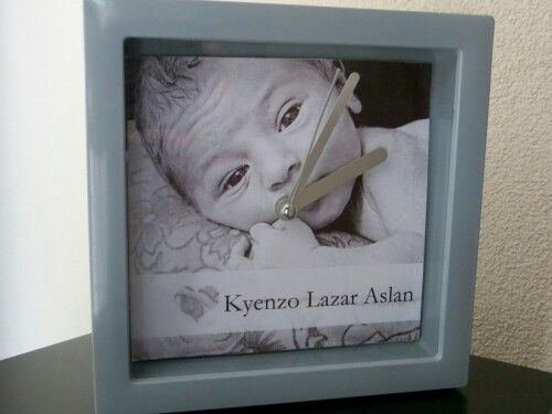 A clock with a birth announcement card as background