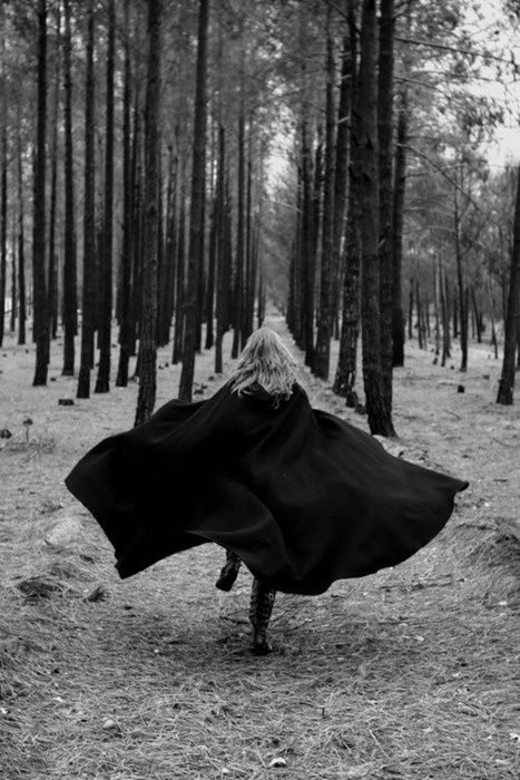 Girl in forest runs and creates joyous magic. B with cloak.