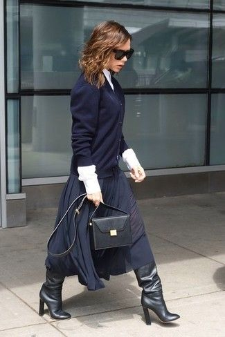 Victoria Beckham wearing Navy Cardigan, White Dress Shirt, Navy Pleated Midi Skirt, Black Leather Knee High Boots