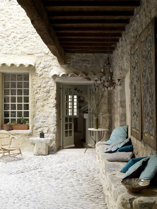 courtyard at House La France in Lagrasse. Nicole Albert uses colorful accents, such as the turquoise pillows, throughout the interior.