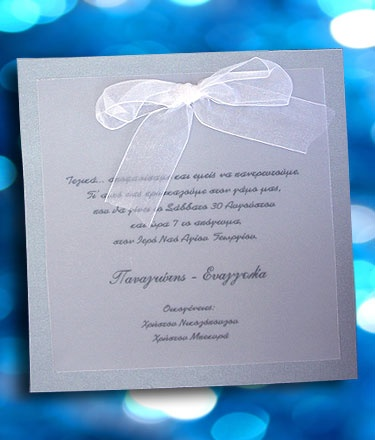 Προσκλητήριο Γάμου σε Τετράγωνο σχήμα με διαστάσεις 17 X 17 εκατοστά κατασκευασμένη από μεταλλικό χαρτί σε ασημένια απόχρωση. Το κείμενο είναι τυπωμένο σε εξωτερική κάρτα κατασκευασμένη από διαφάνεια (ριζόχαρτο). Συνοδεύεται από φάκελλο