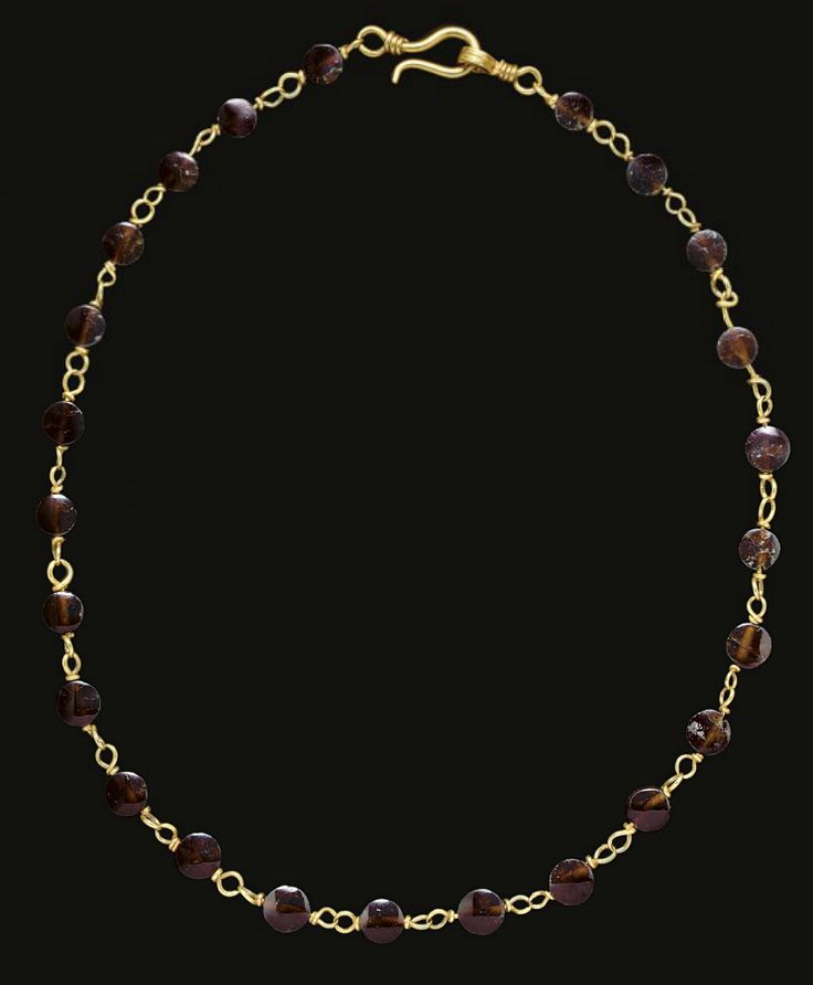 A ROMAN GOLD AND GARNET NECKLACE   CIRCA 2ND-3RD CENTURY A.D.   Composed of twenty-four lenticular garnet beads, each strung on lengths of twisted gold wire coiled into interlocking loops at each end, finished with a hook and loop closure