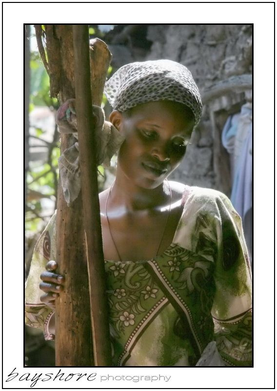 This graceful young woman struck a demure pose as I photographed her in her village in Kenya. by Bayshore Photography @Bayshore Photography
