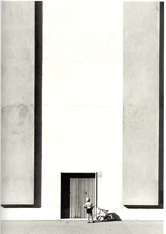 A man standing in front of a door looks very small in comparison to the rest of the photo due to proportion of the man's height to the door and wooden building accents.