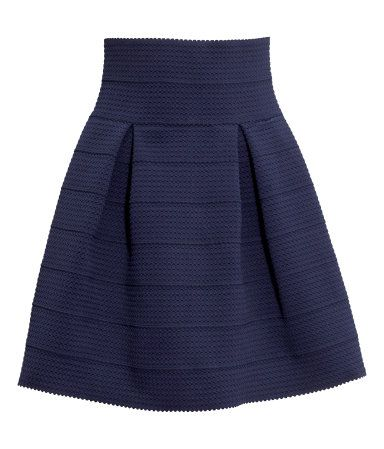 Flared skirt in thick, textured jersey with box pleats. Unlined.