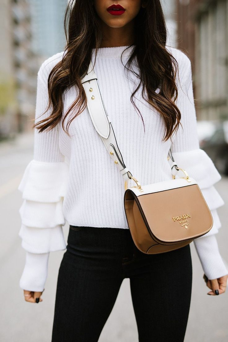 White knit sweater with ruffled sleeves.