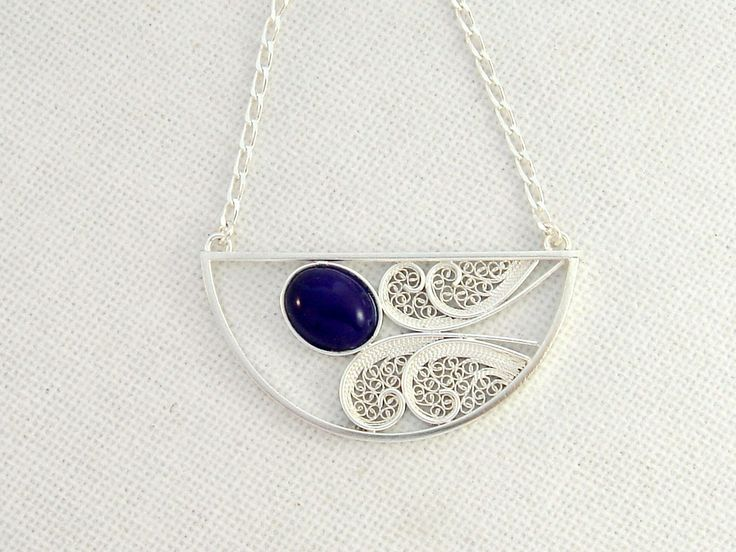 This Sterling Silver Charm Necklace is a delicate and feminin piece, inspired in the floral art nouveau motifs. The pendant is completely handmade and consists in a semicircle with 3,9 cm (1.54'') diameter. This piece is adorned with a blue oval stone and is filled with sterling silver filigree. This piece is very light as the result of the filigree technique.