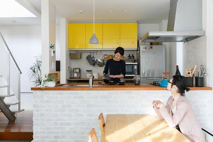 夫婦でコーヒーを楽しむ。キッチンカウンター前面には自分たちで白いブリックレンガを貼った。