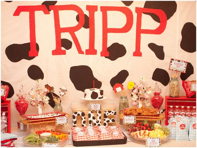 """Oh the cuteness that comes with this ON THE FARM themed Birthday Party! Always a popular theme and definitely a crowd-pleaser, this cute party was sent over by Jennifer Faught of Something Detailed. From the cow print """"ONE"""" to the gingham check treat bags, this party is loaded with cute, little touches.I also love the healthy veggies and fruits added in among the sweets!"""